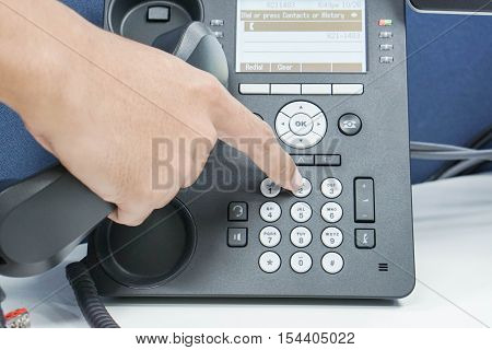man dial numeric button of IP phone for calling