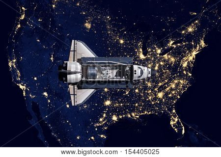 Space Shuttle and aerial night view of the U.S.A. Elements of this image furnished by NASA.
