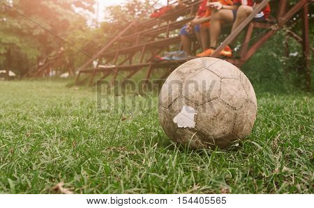 Soccer sunset and old football on green grass