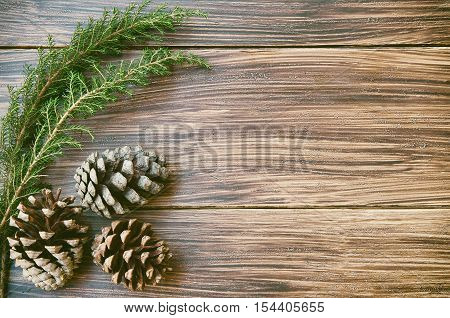 Christmas or New Year background. Natural fir tree brunch and cones on wooden vintage table. Winter holidays concept. Copy space.