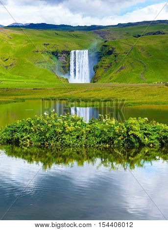 Abounding waterfall Skogafoss reflected in a small pond near the road. An incredible reflection