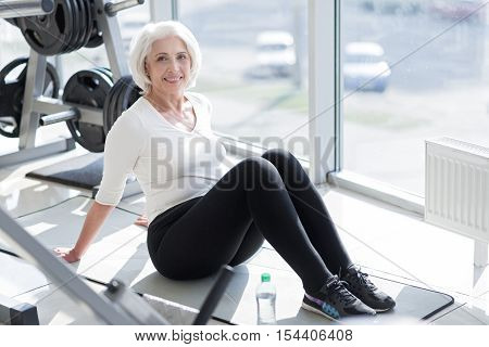 Well deserved rest. Cheerful pleased senior woman smiling and enjoying her rest after working out in the gym.