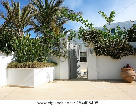 HERAKLION CRETE GREECE - MAY 13 2014: The blue sky and open door on the terrain of villa with flowers palms and amphora in luxury class hotel on the Mediterranean coast of Crete May 13 2014 Greece.