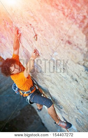 male rock climber. rock climber climbs on a rocky wall. focus on the hand