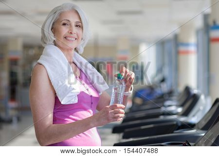 Progressive training. Beautiful happy senior woman smiling and drinking water while having a rest after sport.
