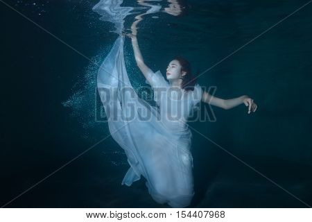 Woman under water on a blue background of the ocean she in white dress dances.