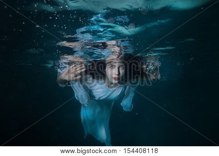 Portrait of a girl under the water she is wearing a white dress.