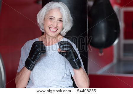 I like box. Delighted pretty senior woman smiling and holding hands like boxer while training in a gym.an holding hands like a boxer.