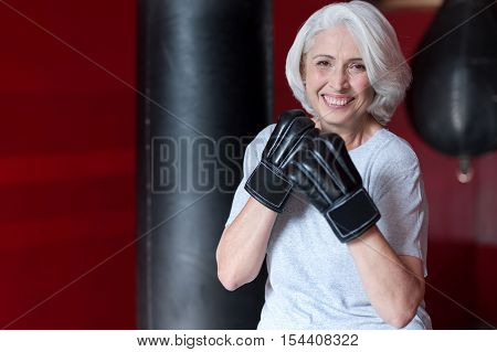 Come to me. Active beautiful happy senior woman smiling and behaving like boxer while exercising in a gym. poster
