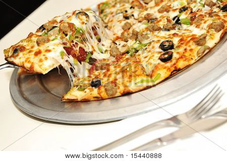 Fantastic pizza, great cheese, fork and knife, serving in restaurant