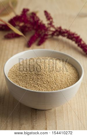 Bowl with amaranth seeds and a twig with flowers on the background