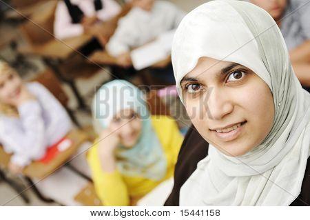 Muslim female teacher in classroom with children pupils (students)