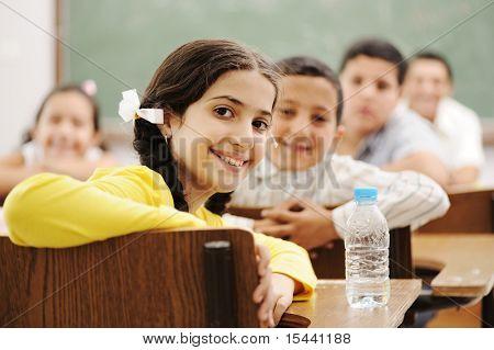 Niños felices lindos en el aula con su profesor