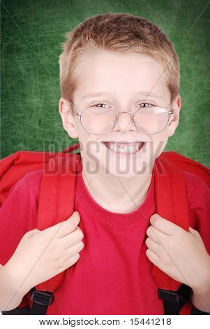First day in school: very cute positive boy wearing glasses without his tooth standing in front of board in class, smiling,  and his bag is on his back