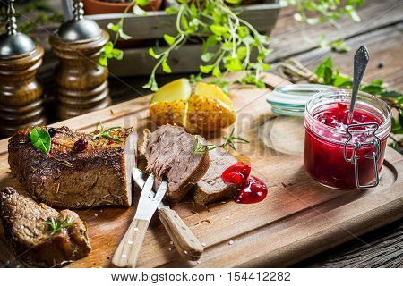 Closeup Of Venison With Cranberry Sauce And Vegetables