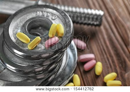 Weight disks and drugs on wooden background