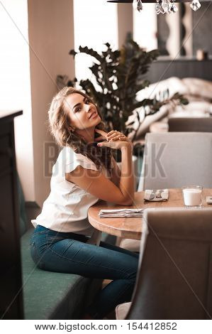 Beautiful blonde girl 20-24 year old sitting in cafe waiting for order. Looking at camera.