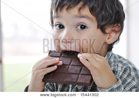 Little cute kid eating chocolate
