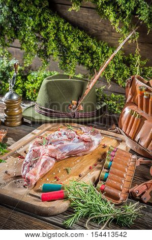 Hunting equipment and venison with herbs on old wooden table