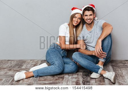 Smiling couple in christmas hats are siting. Siting down. gray background