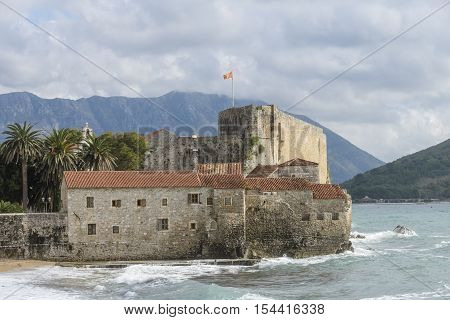 Budva Montenegro - October 21 2016: national flag of Montenegro flying high above old citadel walls while a storm surge is hitting against the citadel walls and flooding the nearby beach