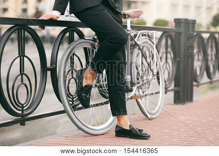Young businessman with bicycle standing near handrail on the street
