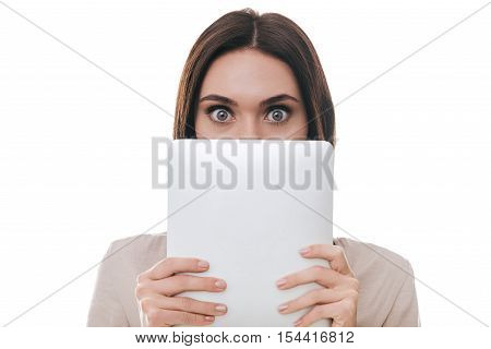 No way! Frustrated young woman covering part of her face with digital tablet and staring at camera while standing against white background