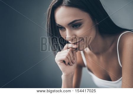 Thoughtful beauty. Attractive young woman holding hand on chin and looking thoughtful while sitting against grey wall