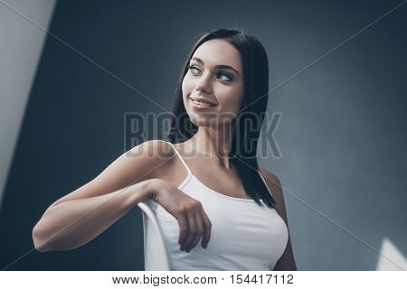 Cheerful seductress. Attractive young woman sitting on chair and looking over shouder with smile while sitting against grey wall