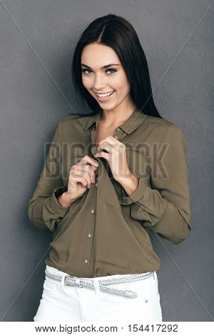 Unbuttoning her shirt. Attractive young woman unbuttoning her shirt and looking at camera with smile while standing against grey wall