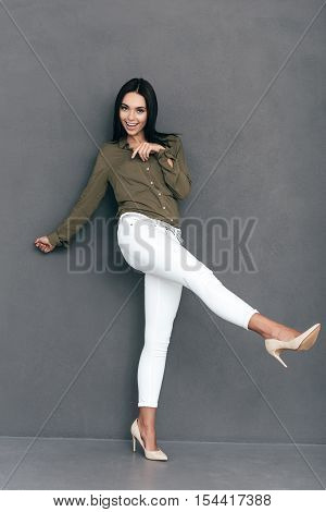 Playful and beautiful. Full lenght of attractive young woman in smart casual wear posing against grey background and looking happy