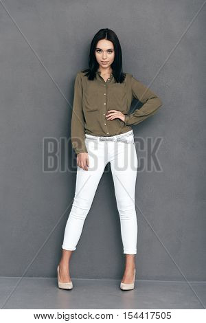 Confident in her style. Full lenght of attractive young woman in smart casual wear posing against grey background