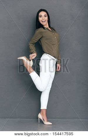 Look at my new heels! Full lenght of attractive young woman in smart casual wear posing against grey background and looking happy