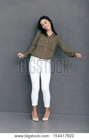 She loves dancing. Full lenght of attractive young woman in smart casual wear dancing against grey background and looking happy