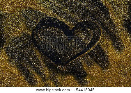 Sand painting concept. Golden glitter sand texture spread over black surface with heart shape, abstract background. Yellow dusty shimmer decoration, shiny and sparkling.