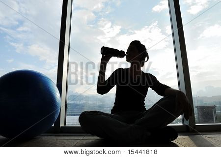 Fitness sporty girl silhouette excercising and drinking a water