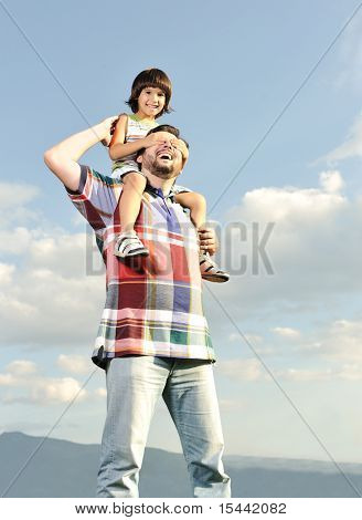 Young father and his son on back, piggyback, pica-boo playing, outdoor scene, love and care