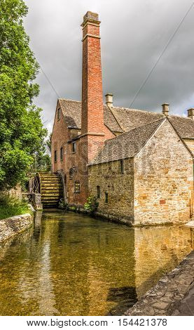 19th century watermill in the English Cotswold village of Lower Slaughter showing the intact waterwheel, chimney and river which powers the mill.