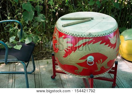 Red drum with asian motifs on the base. Drumsticks are located on the drum.