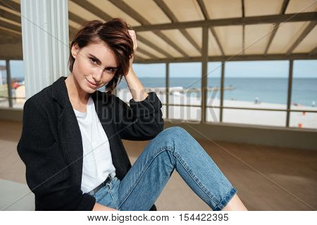 Smiling attractive young woman sitting in arbour near the sea