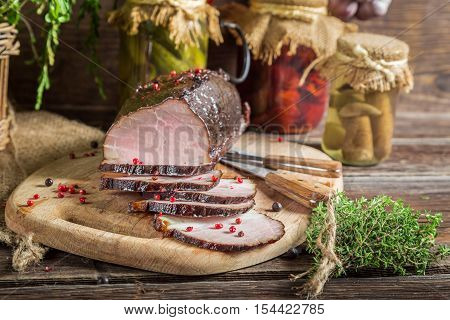 Freshly sliced smoked ham and marjoram on old wooden table