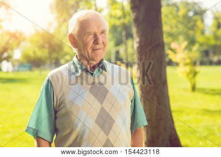 Senior man outdoors. Old guy slightly smiling. Purity of reason. Wisdom comes with time.
