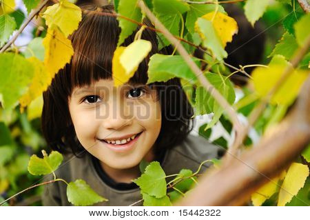 Happy childhood outdoor, happy faces between the leaves of the trees in forest or park, look for more in my porftolio