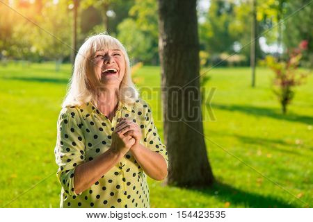 Elderly woman laughing. Happy lady outdoor. Greatest joy in life. All troubles left behind.