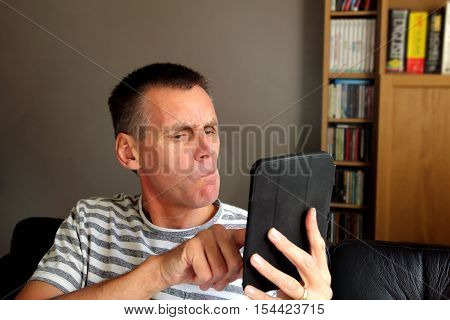 Puzzled And Confused Older Man Using Tablet Computer