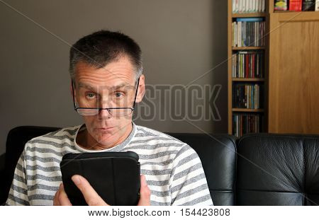 Serious Stern Man Looking Up Over His Glasses While Using Tablet Computer