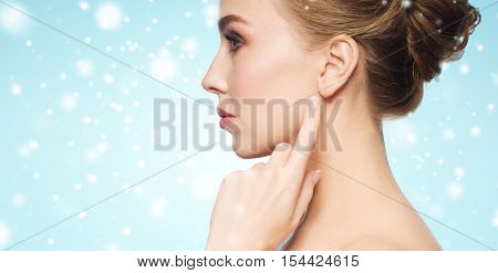 health, people, winter and beauty concept - close up of beautiful young woman pointing finger to her ear over blue background and snow