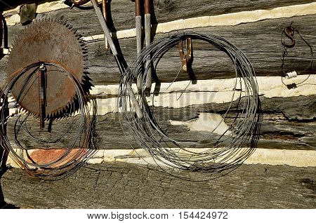 The wall of an old log cabin is decorated with rolls of wire tools, and a huge circular saw blade.