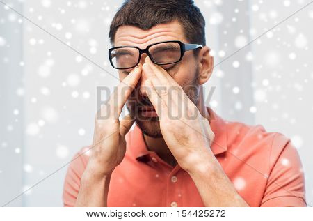 people, eyesight, stress, overwork and business concept - tired man in eyeglasses rubbing his eyes at home or work over snow