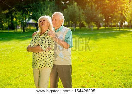 Couple of senior people outdoors. Man smiling and hugging woman. I can feel your heartbeat. Strength of true feelings.